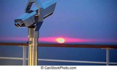 Telescope in shell near fence on deck of ship - Telescope in...