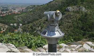 Telescope on tourist path in mountains