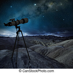 telescope tripod pointing the milky way in a desert...