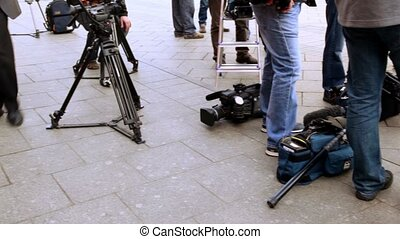 Television equipment lay on ground near operators legs,...