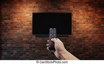 Television on brick wall with hand using remote control
