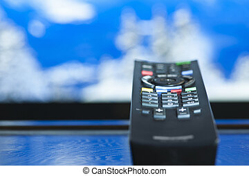 Television remote control closeup pointing at tv