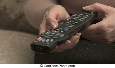 Television Remote - Woman operates TV remote control