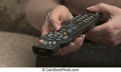 Woman operates TV remote control