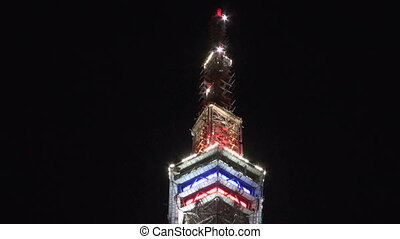 Television tower at night decorated with fires