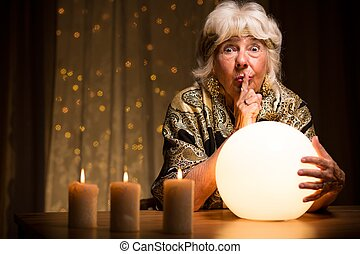 Telling fortune from magic ball - Female seer telling ...