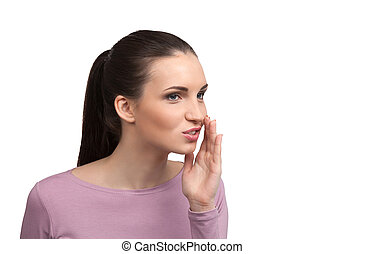 Telling gossips. Beautiful young woman saying something and holding hand near mouth while standing isolated on white