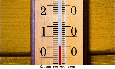 Red mercury showing temperature of the air is rapidly growing up in a wooden thermometer, which weighs on the wooden wall of a house. Timelapse