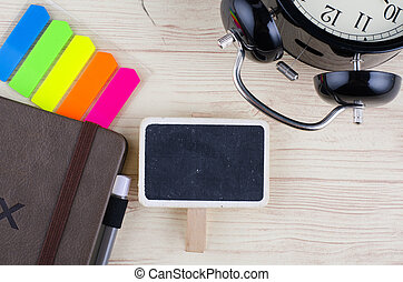template background with wooden signage for text, alarm clock, sticky paper and diary  on desk