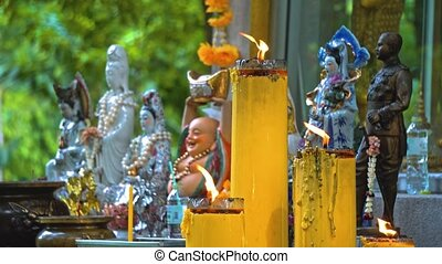 temple buddha under the trees. Buddhism in Asia. candles and flowers. place of religious worship of believers