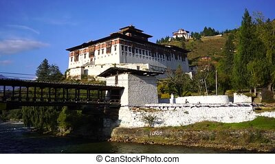 Temple Dzong and religious prayer flags in valley, Bhutan - ...