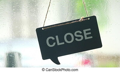 Temporarily closed sign for in small business activity during with raining. Close up on a black wood tag placard in the window