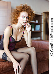 Tempting attractive woman in corset and stockings sitting on sofa