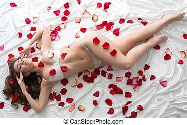 Tempting model in erotic lingerie with rose petals. Top view