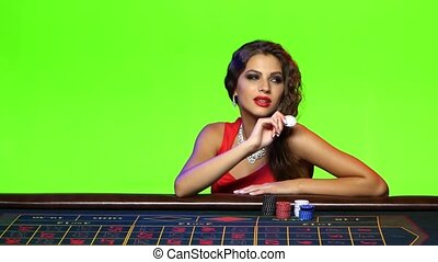 Luxury girl sitting at the poker table in a casino, tempting offer from a girl dressed in evening red dress, on the neck jewelery, plays with a chip, green screen