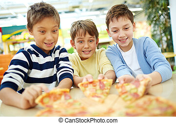 Tempting pizza - Three boys sitting thrilled with pizza