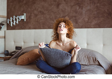Tempting sensual  woman sitting and resting on bed