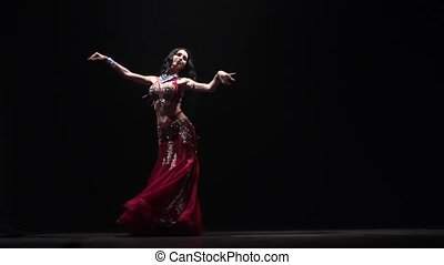 Tempting sexy traditional oriental belly dancer woman dancing . Black background. Slow motion
