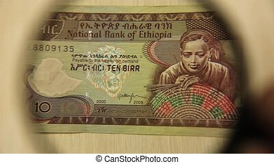 View a Ten Ethiopian Birr bill lying on a table with a magnifying glass. concept of business and finance.