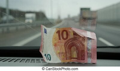 Ten euros placed in the car to the front glass. Close up -...