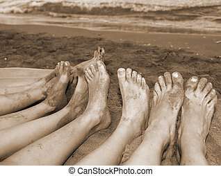 feet of a family by the sea on the beach