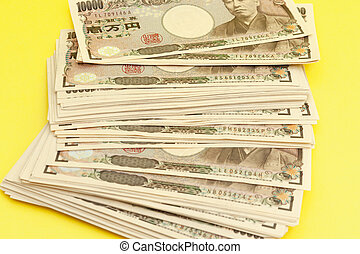 Ten thousand yen (10,000 yen) banknotes stacked. Japanese money. Paper money. Isolated on yellow background. Top view. Close-up.