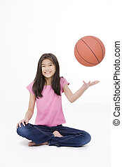 Ten year old Asian girl holding basketball, isolated on...