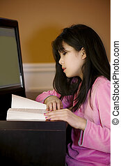 Ten year old Asian girl reading at desk, by computer
