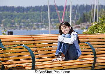 Ten year old girl enjoying the sun on bench by the lake