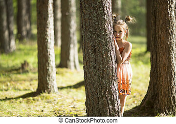 Ten-year-old girl looks out from behind a tree.