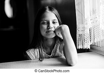 Ten-year-old girl posing for the camera sitting at the table. Black and white photo.