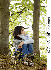 Ten year old girl sitting quietly in woods