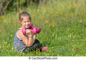 Ten-year-old girl with dumbbells