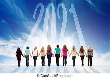 Ten young women walking hand in hand towards 2021. Happy New 2021.
