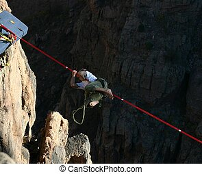 Tenacity - Slack line walker clinging to line stretched over...