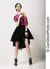 Tendency. Glamorous Fashion Model in Modern Clothes posing in Studio