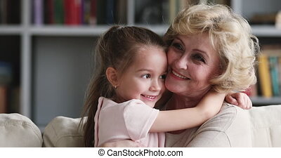 Tender affectionate older adult grandma hugging cute little granddaughter bonding cuddling, happy 2 two age generations family grandparent and grandkid embrace enjoy sweet moments of love concept