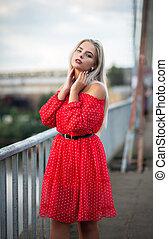Tender blonde girl wearing trendy red dress, posing on the bridge in the evening