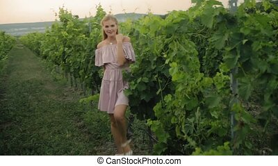 Tender blonde in the pink dress walking along the green vineyard
