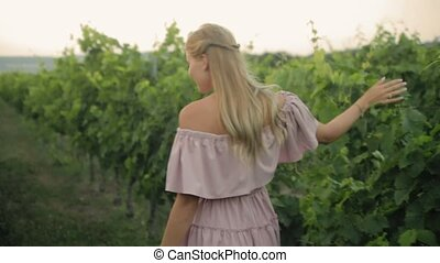 Tender blonde in the pink dress walking along the green vineyard