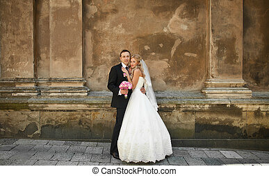 Tender bride leans to a groom standing at the old wall