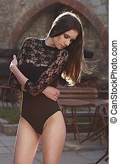 Tender brunette model in lace lingerie posing at the street