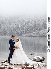 Tender couple in love. brides mountain near the lake in winter