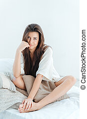 Tender cute young woman sitting on bed