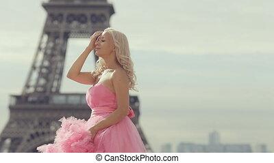 Tender girl in a pink fairy long dress posing near the Eiffel Tower in Paris