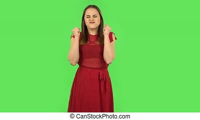 Tender girl in red dress is looking at camera with anticipation, then very upset. Green screen