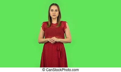 Tender girl is reporting and telling a lot of interesting information. Female with medium brown hair and natural makeup in red light polka dot dress on green screen at studio