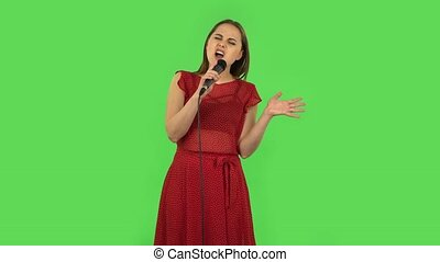 Tender girl in red dress is singing into a microphone and moving to the beat of music. Green screen