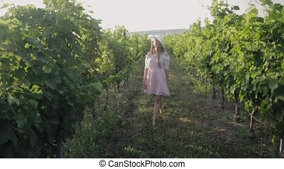 Tender girl with curls in the hat walks through the vineyard