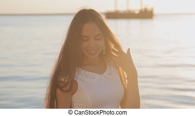Tender girl with long hair posing near the sea at sunset